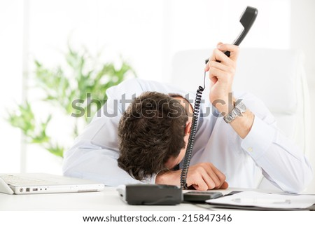 Tired young Businessman holding telephone and leaning his head on the table in the office.