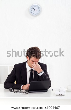 tired young businessman massage his eyes after hard working in office