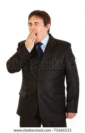 Tired young  businessman yawning isolated on white