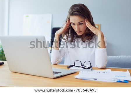 Tired young businesswoman struggling to keep working holding head and looking down in office