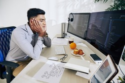 Tired young Indian programmer almost sleeping at his desk after working on difficult project all day long