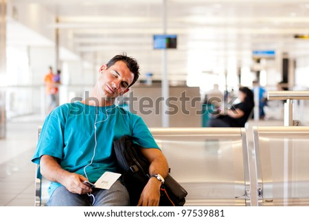 tired young male traveller sleeping in airport
