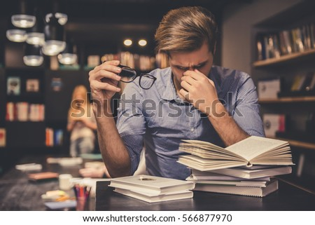 Tired young man is holding eyeglasses and massaging his nose bridge while working hard in the modern library #566877970