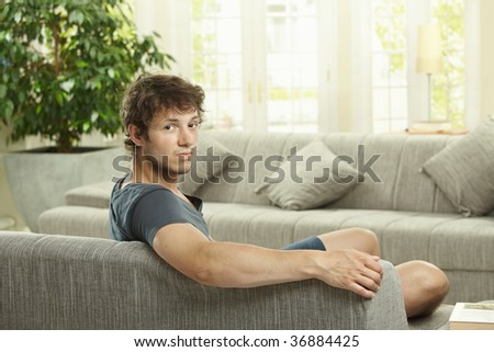 Tired young man sitting on couch at home, looking bacdk at camera.