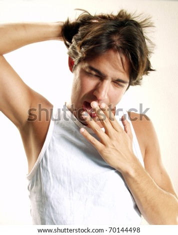 Tired young man yawning on white background.  Getting up at morning.