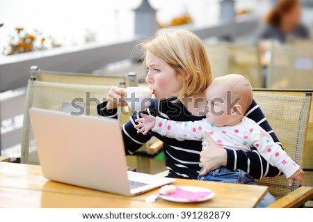 Tired young mother working oh her laptop and holding 6-month daughter  #391282879