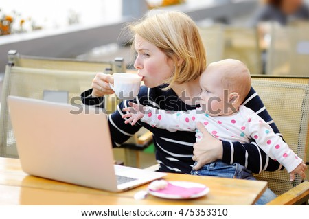 Tired young mother working oh her laptop, holding daughter and drinking coffee #475353310