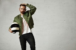 Tired young motorbiker in green bomber jacket, black jeans and white t-shirt adjusting his hairstyle and holding his white helmet