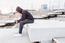 Tired young slim man jogger athlete rests after a morning training in urban space. Concept of self-organization and building a slim body. Place for advertising content