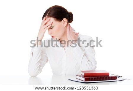 Tired young woman at a table with books, white background