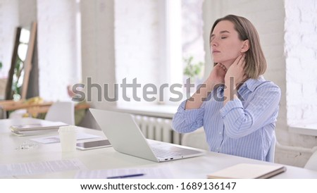 Tired Young Woman having Neck Pain in Modern Office
