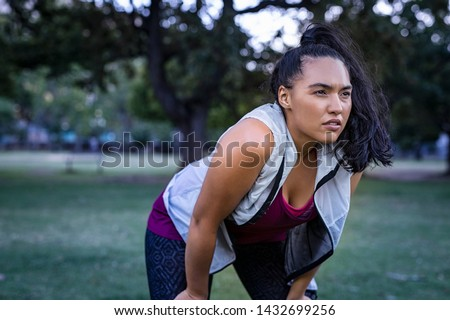 Tired young woman resting after jogging outdoor. Determined latin girl sweating and taking a rest after running hard. Exhausted curvy woman relaxing after running in park with breathing exercise.