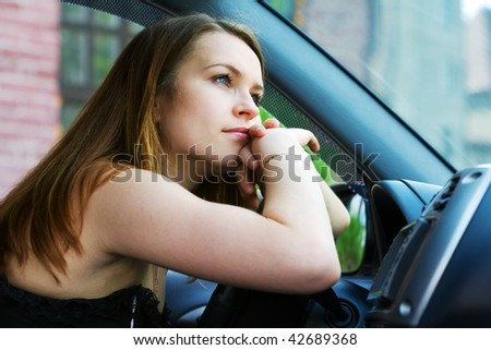 Tired young woman resting in the car.