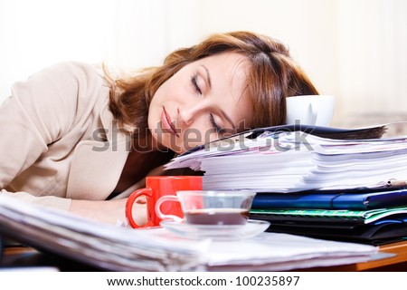 Tired young woman sleeping on the table