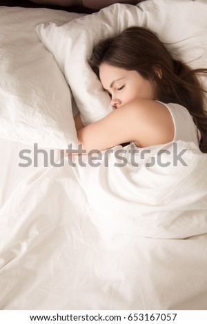 Tired young woman sleeps well in soft bed with white sheets. Female teen peacefully resting with eyes closed in bedroom, enjoys sweet dreams. Perfect conditions, comfortable good night sleep. Top view