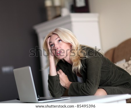 Tired young woman using laptop