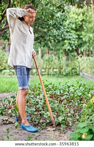 Tired young woman with hoe working in the garden bed