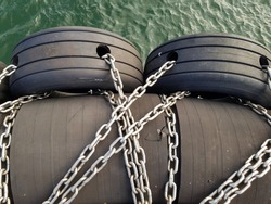 tires on steel chains are along the berth for boats