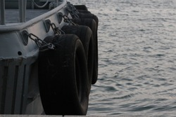 Tires/Tyres at the back of a Coast Guard boat/vessel to protect it when it berths at a jetty