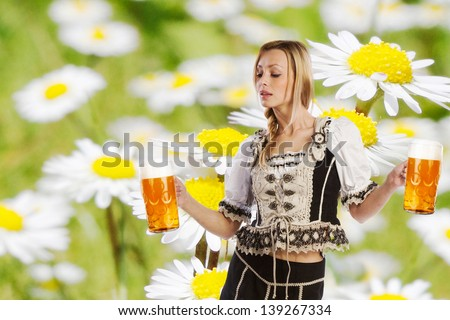 tiroler summer party with a sexy woman or girl in traditional austrian or german oktoberfest clothes holding a big glass of beer in her hands and on the background white and yellow farmland flowers