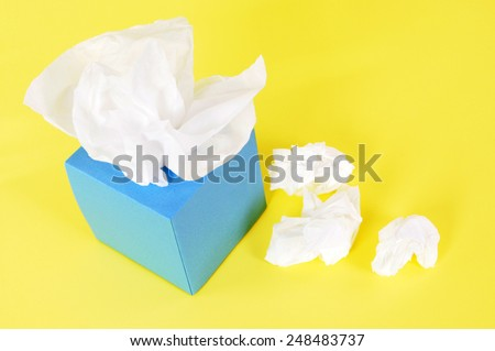 Tissue box :  Kleenex style, used tissues, yellow background.
