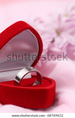 Titanium engagement ring with diamond in a heart shaped box on pink background with pink hyacinth. Shallow dof