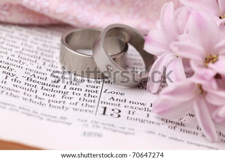stock photo Titanium wedding rings on the Bible open to 1st Corinthians 13