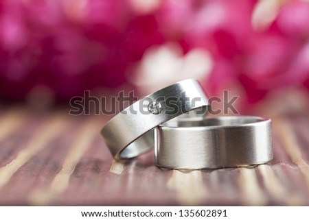 Titanium wedding rings with red hyacinth in the background. Shallow dof