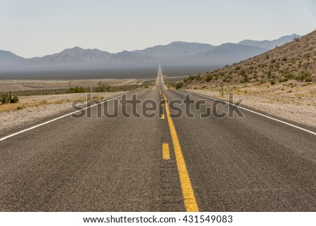 Title: American road trip in desert and mountain area with yellow line in the middle of the road; road straight long road with yellow middle line, Big long straight road with no car with yellow line