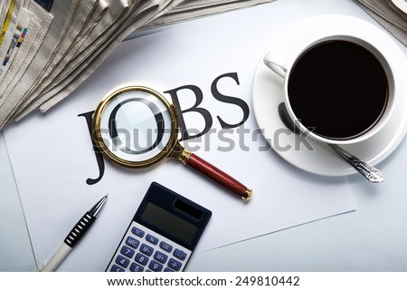 title jobs with loupe, pen, newspapers, cup of coffee and calculator