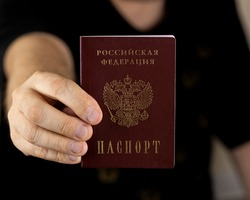 Title: Passport of the Russian Federation. A human hand with a Russian passport in close-up. The concept of obtaining citizenship of the Russian Federation. Close-up, selective focus, blur.