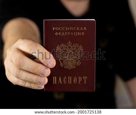 Title: Passport of the Russian Federation. A human hand with a Russian passport in close-up. The concept of obtaining citizenship of the Russian Federation. Close-up, selective focus, blur. Stok fotoğraf ©