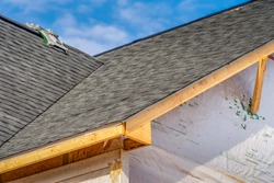 Title: Single family home under construction with fiber cement roof installed, gutter holders, soffit, truss