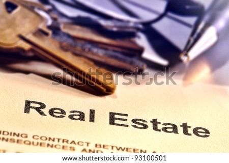 Title word real estate on a Realtor broker document contract page with set of house keys and ink pen in a realty brokerage resale office (fictitious document with authentic legal language)