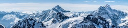 Titlis mountain. Beautiful panorama of snowy alps in white-blue tones.