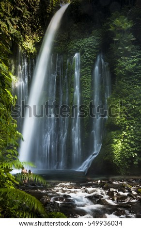 Tiu Kelep waterfall in Senaru, Lombok, Indonesia. Tourists from overseas were enjoying the waterfall.  #549936034