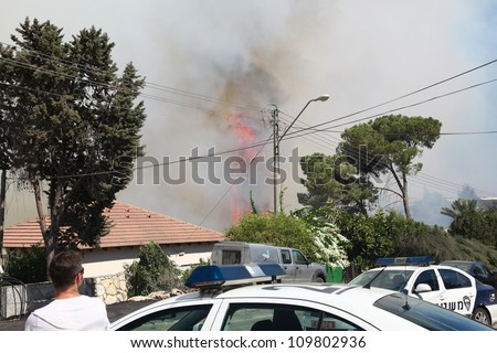 TIVON, ISRAEL - AUGUST 09: Fire erupts above the streets after a forest fire breaks out in Kiryat Tivon. Rescue workers struggle to prevent further damage. Tivon, Israel August 09, 2012