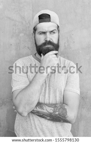 To beard or not to beard. Thoughtful hipster thinking on grey wall. Hipster touching thick beard hair on unshaven face. Bearded man in trendy hipster style. Brutal hipster wearing casual baseball cap.