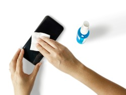 To clean your phone to prevent spread of Coronavirus, use a 70% isopropyl alcohol wipe. Top view isolated on white background.
