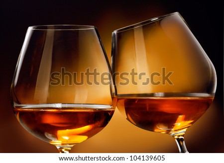 To clink two glasses of Cognac or Brandy liquor in front of a brownish background.