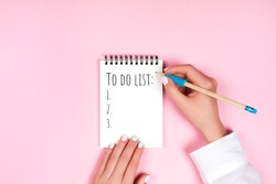 To do list in spiral notepad. Trendy pink background, flat lay style.
