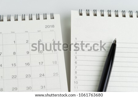 To do list or work task priority list with date concept, black pen on notepad with list of numbers with flip calendar beside on table.