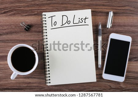 To do list Top view of coffee cup and clear notepad with white pen and blank smart phone on the office desk.  #1287567781