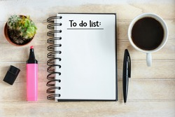To do list written in a notebook / Notebook with an to do list on wooden desk with cup of coffee