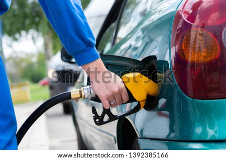 To fill the machine with fuel.   Gas station pump. Man filling gasoline fuel in car holding nozzle #1392385166
