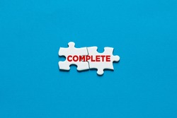 To finish a task, job or project concept. Two connected puzzle pieces with the word complete.