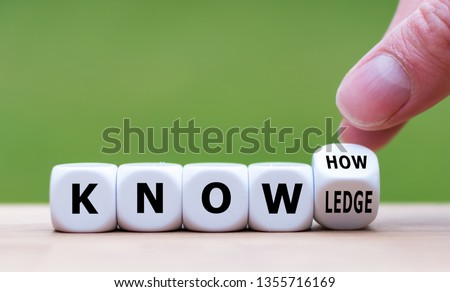 To have know-how or to have knowledge. Hand turns a dice and changes the word  'know-how' to 'knowledge'. Foto stock ©