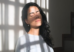 To overcome the effects of quarantine, a brunette woman takes advantage of the morning sun's rays near a window inside her home. Vitamin D. Improves immunity. Health. Social isolation. Pandemic