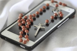 To talk to God,  color photo, still life of mobile phone and rosary with cross