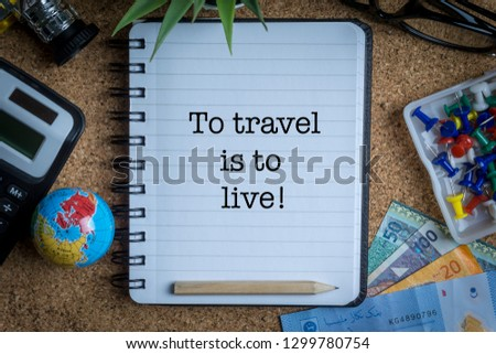 TO TRAVEL IS TO LIVE inscription written on book with globe,eyeglasses, calculator, camera, pencil and vase on wooden background with selective focus and crop fragment. Business and education concept Stock fotó ©